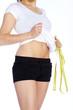Sportliche Frau mit Maßband und flachem Bauch