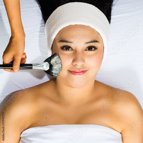 Cosmetics - Asian woman gets a facial mask