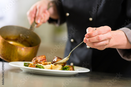 canvas print picture Chef in hotel or restaurant kitchen cooking