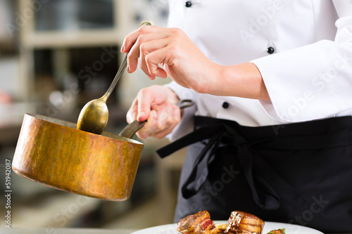 Female Chef in restaurant kitchen cooking