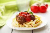 Italian meatballs with penne pasta in tomato sauce