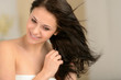 Young smiling girl blow drying her hair