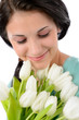 Smiling woman holding bouquet of white tulips