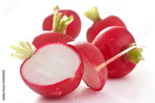Red radish cut in half on white