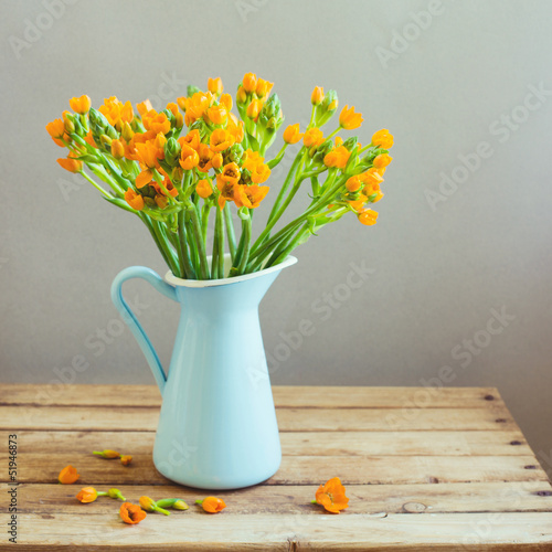 Orange flowers in blue jug on wooden table