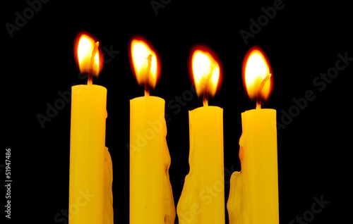 yellow candles isolated on black background
