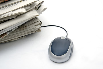 pc mouse next to a pack of newspapers