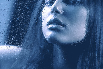 Portrait of Beauty Girl behind the Wet Glass
