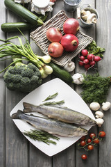 Two raw, fresh rainbow trouts among vegetables.