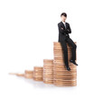 Successful business man sitting on money stairs