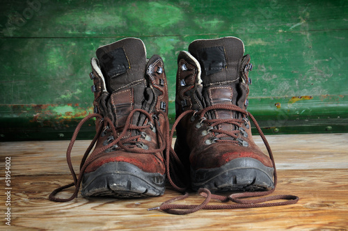 Used boots on old  wooden floor - 51954002