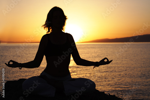 beauty girl in lotus pose on sunrise beach