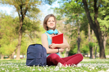 Beautiful female student with book and headphones sitting on a g