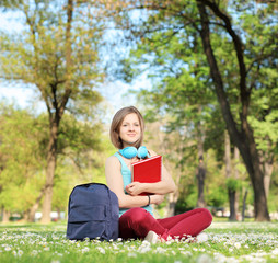 Beautiful young female student with book and headphones sitting