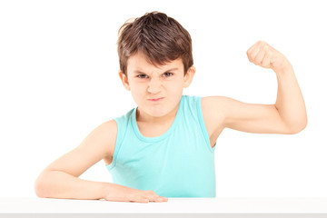 A mad child showing his muscles seated on a table