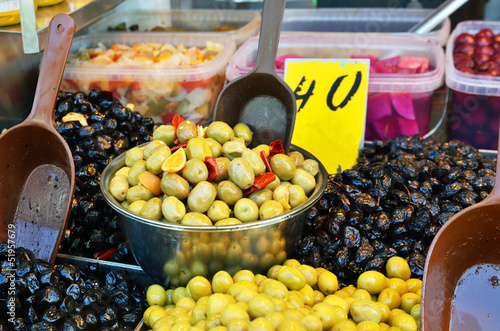 assortment of olives, pickles and salads in bowls on market stan