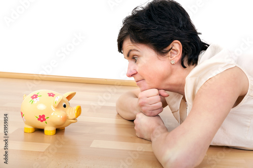 Woman looks thoughtfully at the piggy bank
