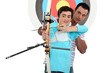 Man and a teenager practicing archery