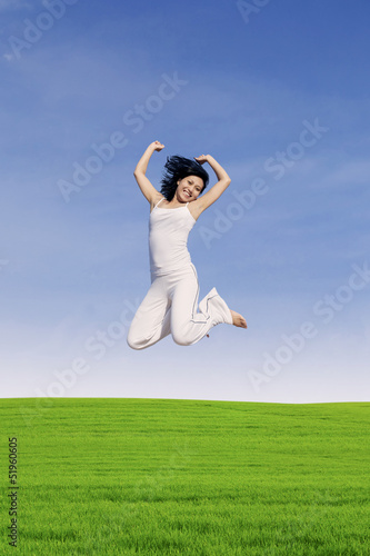 Beautiful woman jump on green field