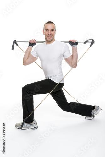Sportlicher junger Mann bei einer Gymnastikübung mit einem Gymn
