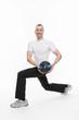 Sportlicher junger Mann bei einer Gymnastikübung mit Medizinbal