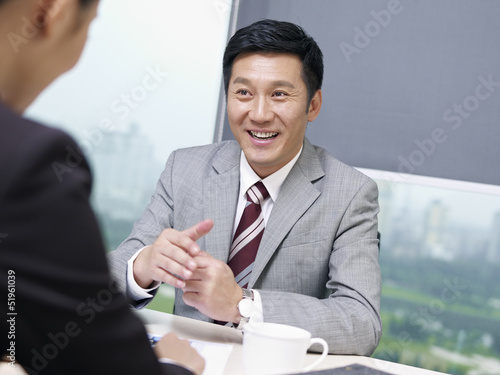 asian business people talking in office, looking excited