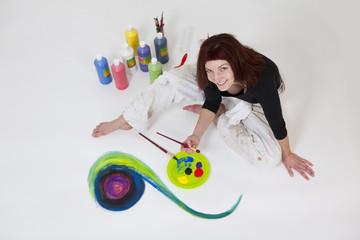 Malering malt mit Farben auf dem Boden