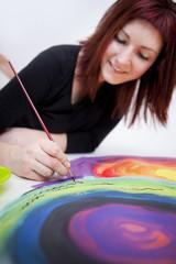 junge Künstlerin macht filigrane Pinselstriche