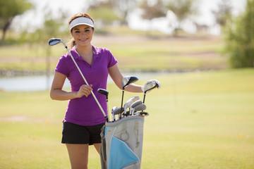 Happy female golfer grabbing a golf club from her bag