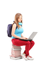 A smiling student with backpack typing on a laptop and sitting o