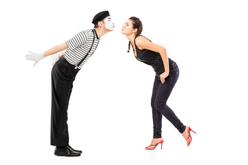 Full length portrait of a male mime artist and a young woman abo