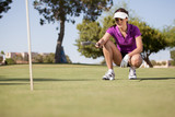 Beautiful female golfer planning how to get the ball in