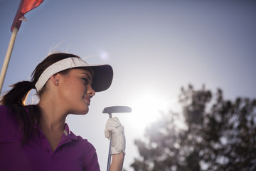 Cute Latin female golfer with copy space and sun flare