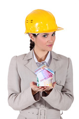 Female architect holding house lade from bank notes