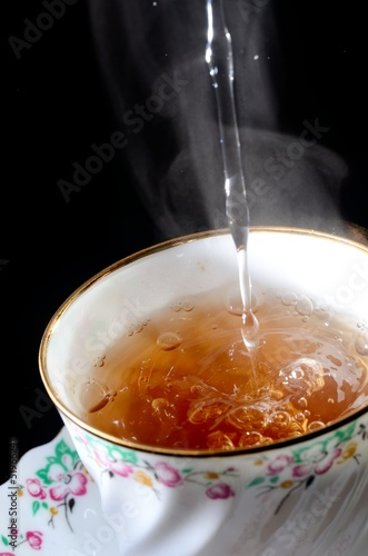 filling tea cup isolated on black