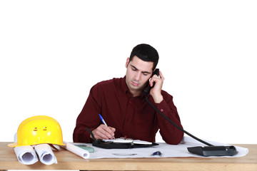 Architect sat at desk making call
