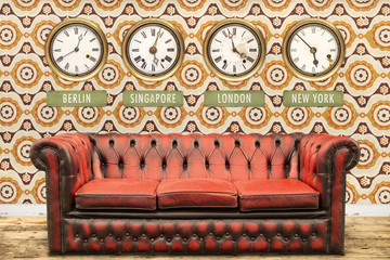 Retro chesterfield sofa with world time clocks on a wall