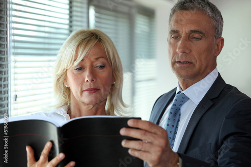 Senior business couple reading through contract
