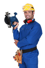 young blue collar with protective equipment and sander machine