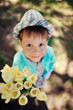 on the nature of the little boy in a blue shirt with a bouquet o