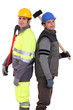 Tradesmen standing back to back and holding tools
