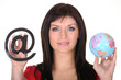 Woman holding globe and at symbol