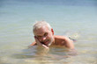Grey-haired man laying in the sea