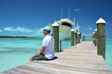 A man fishing on the wooden jetty. Exuma, Bahamas