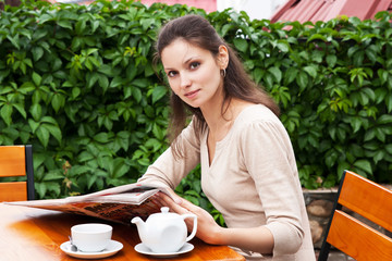 Девушка на веранде читает газету