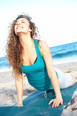 Happy pretty woman at the beach doing yoga