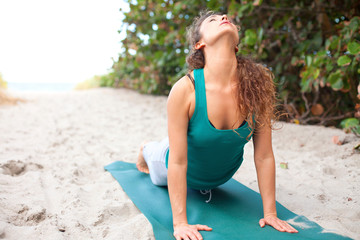 pretty female doing yoga at the beach
