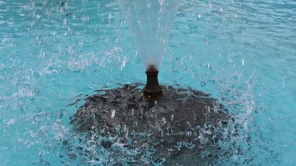 Water spray of fountain on a turquoise background