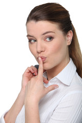 Portrait of a cheeky businesswoman with her finger on her lips