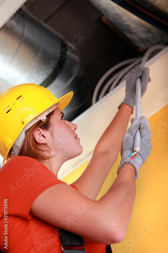 Female electrician pulling cables